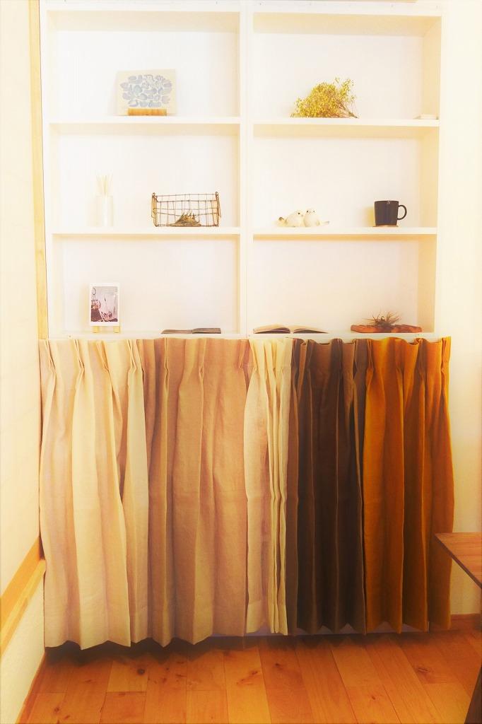 住宅ショールームの造作収納棚に設置した目隠し兼展示用の麻のカーテン
